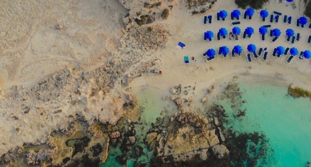 This is a photo from the drone photography bible website. The article is a review of the dji mavic air. This photo is of an beach and rock from above by a mavic air