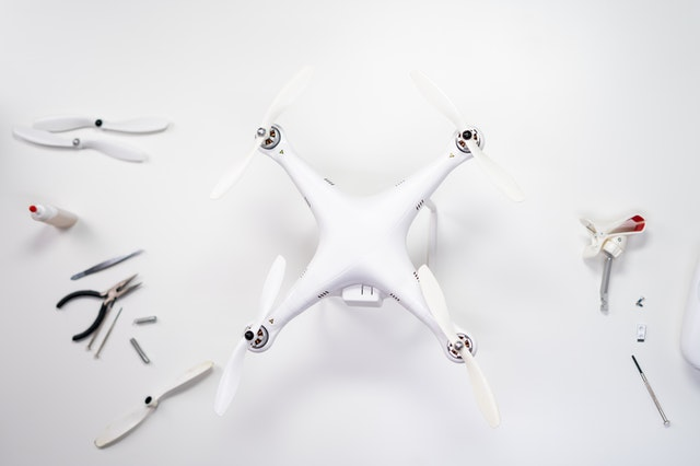 A white drone with spare parts and tools to fix it. -Photo of a drone from the drone photography bible article Things to Check When Buying a Used Drone