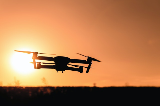 A drone flying at sunset - Photo of a drone from the drone photography bible article Things to Check When Buying a Used Drone