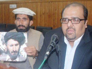 Noor Khan (left) holds a photo of his father killed in a US drone strike, alongside his lawyer, Shahzad Akbar