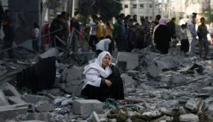 A woman sitting in rubble after her Rafah home was flattened by an Israeli strike. Photo: AP