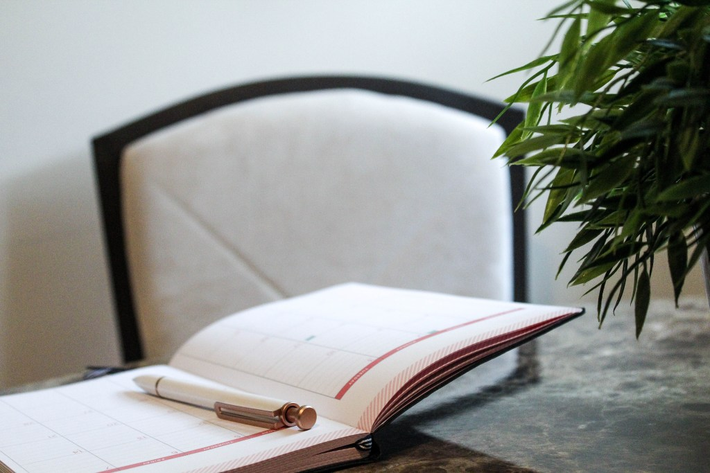 open notebook with pen on table with plant and chair