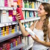 Woman choosing shampoo at store