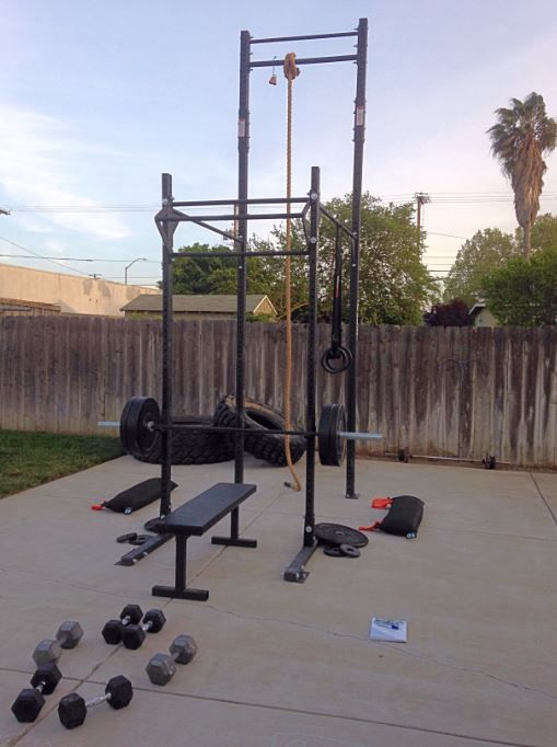 A power cage with barbell and bench, plenty of weights and a rope climbing attachment. A setup any marine would be proud of.