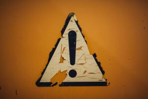 A warning exclamation point in peeling paint on an orange wall