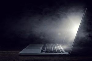 A laptop glows in the dark