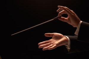 Hands of an orchestra conductor holding a baton in midair.