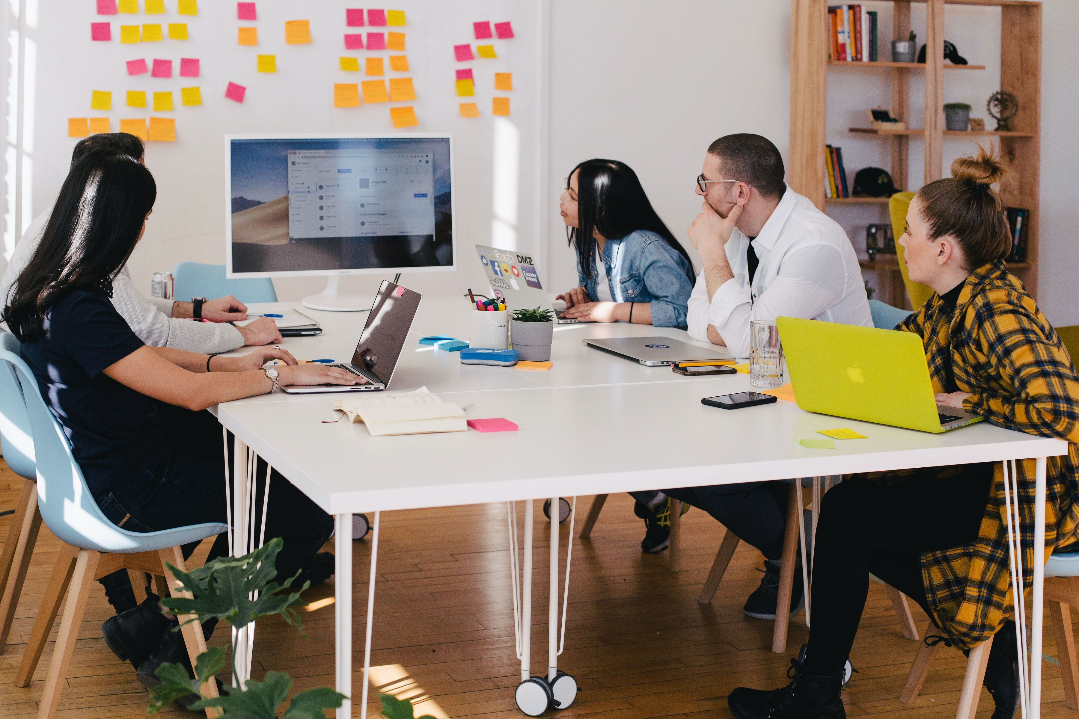 A group of people in an office sit at a table with a monitor, and array of post it notes on the wall.