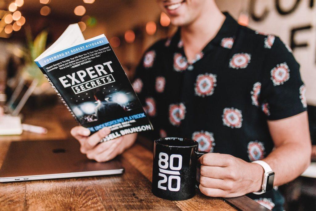 man reading expert secrets playbook