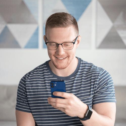 Tom smiling at phone