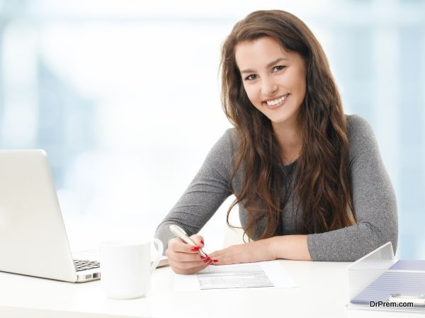 Portrait of young businesswoman fill the form while sitting at office.