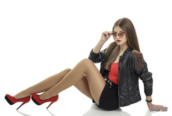 Beautiful sexy woman wearing sunglasses, black leather jacket, dark shorts and red high heels shoes posing over white background.