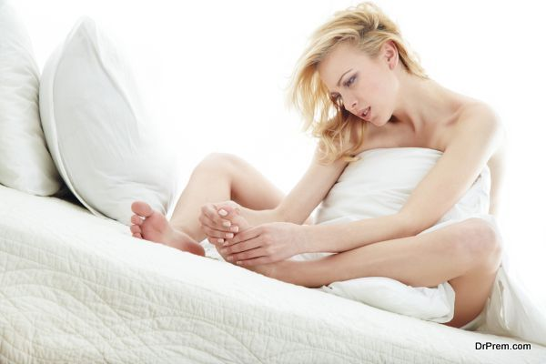 Blond lady covered by blanket in the bed room suffering from the callosity