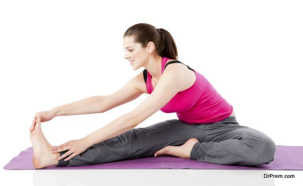Happy young woman stretching legs on exercise mat over white background