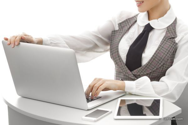 Close-up on arms of confident business woman working on laptop tablet and phone, selective focus