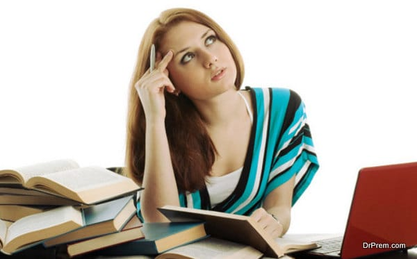 Young woman sitting at a desk among books and laptop on a white background