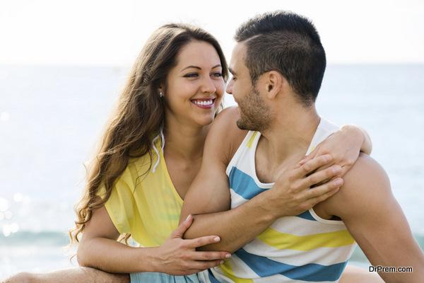 Happy twosome having romantic date on sandy beach