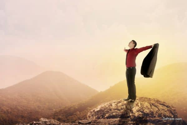 Asian business man standing on the top of mountain, raise hand and open his suit