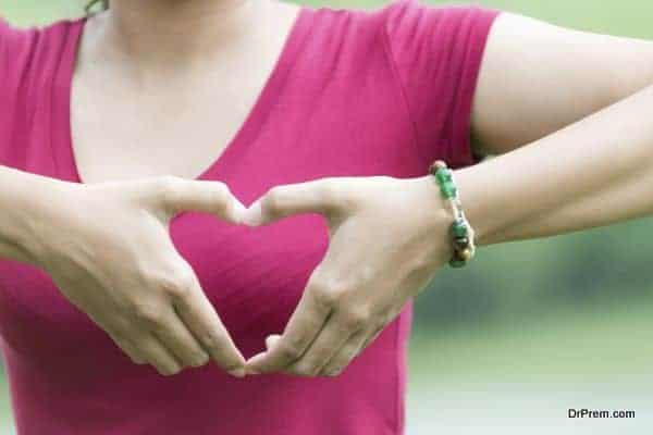 Female hands in the form of heart on nature