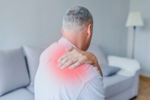 middle aged man suffering from shoulder pain