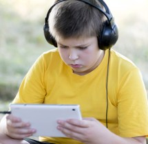 Boy in headphones looking tablet computer on the nature