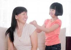Asian child doing shoulder massage to her mother
