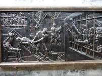 There are many embossed metal depictions of the torture of prisoners