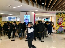 Men line up to check out the latest Pokemon merchandise while a screen advertises women's underwear