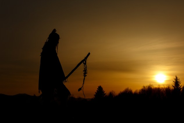 silhouette of native american shaman with pikestaff on background of sunset beutiful in mountains