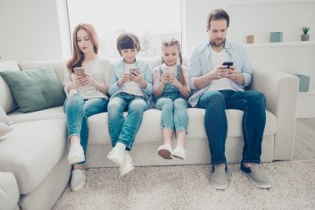 Portrait of family with two kids having holding smart phone electronic device.