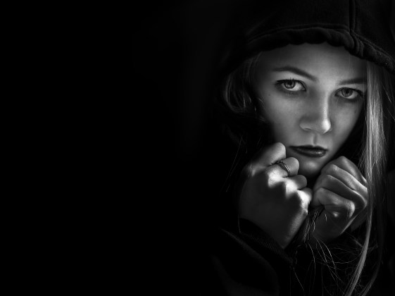 scared girl in hood looking at camera on black background with copyspace monochrome