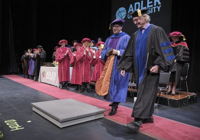 Two men walk of stage at a university commencement ceremony