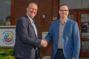 Voor het bedrijfspand in Dordrecht schudden Michel Zijderveld en Johan den Houter elkaar de hand