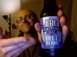 Rich holds a bottle of EBC Blue Berry Wheat Beer