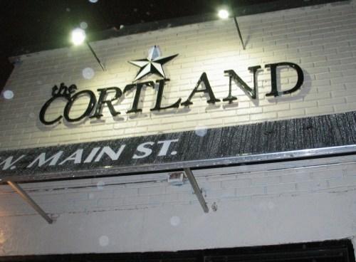 The Cortland facade on a rainy night