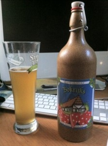 A pilsner glass filled with the cloudy golden ale, Bokrijks, next to the ceramic bottle of Bokrojks.