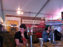 A cheeky gentleman and a woman stand behind the taps at Beau's All Natural station in Toronto's Festival of Beer