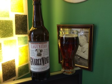 A bottle of Lagunitas GnarleyWine with a glass filled with the dark caramel-colored beer.