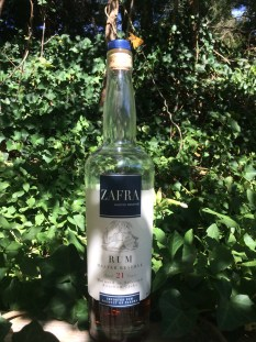 A golden moth sits atop a bottle of Zafra Master Reserve. The bottle is half empty, at it stands amongst a background of green ivy.