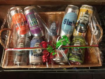 Eight cans of Port Jefferson Brewing beer and a pint glass with Port Jefferson Brewing's logo in a wrapped gift basket.