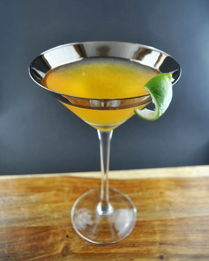 Cocktail in silver rimmed glass with lime garnish on top of cutting board