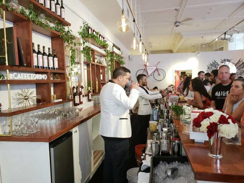Busy cocktail bar with several bartenders in white and many bottles on the shelf behind them