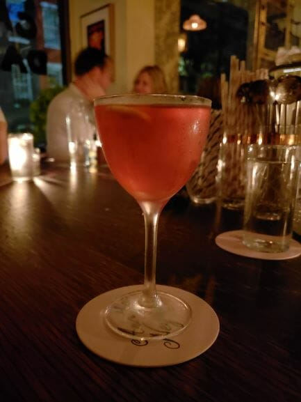 Reddish cocktail on white coaster with several people behind