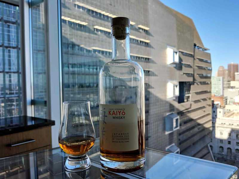 Bottle of whisky next to glass filled with whisky with large building behind it