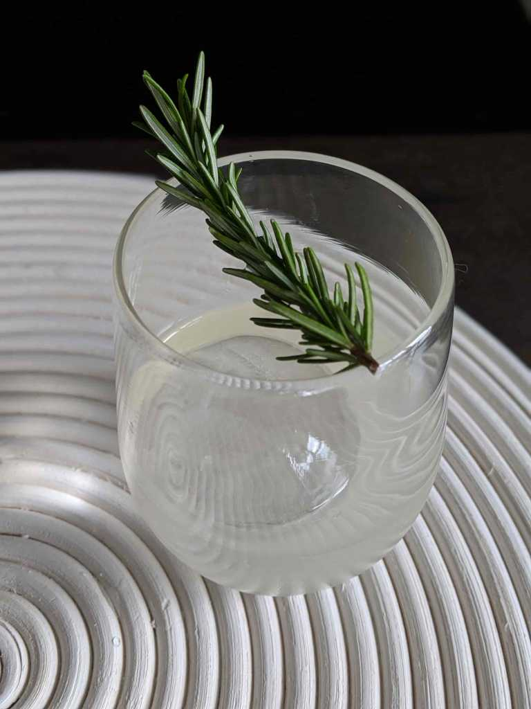 Ice cube with sprig in glass with clear cocktail on white placemat