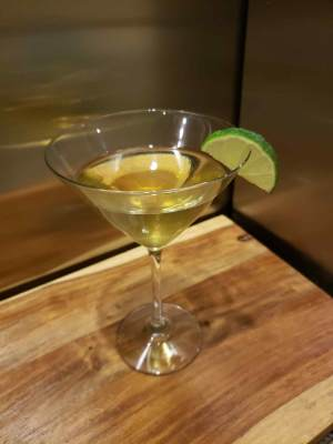 Cocktail ontop of cutting board with lime garnish