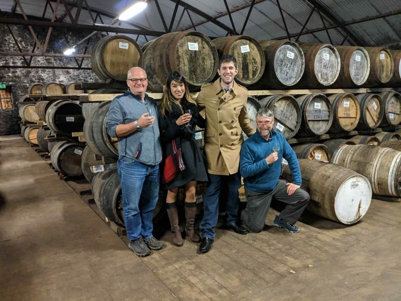 Three men and one women in warehouse with may casks