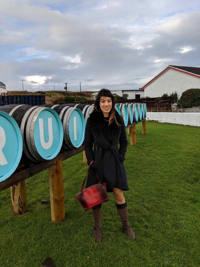 Woman next to whisky barrels.