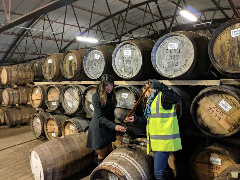 Woman getting whisky in front of many casks