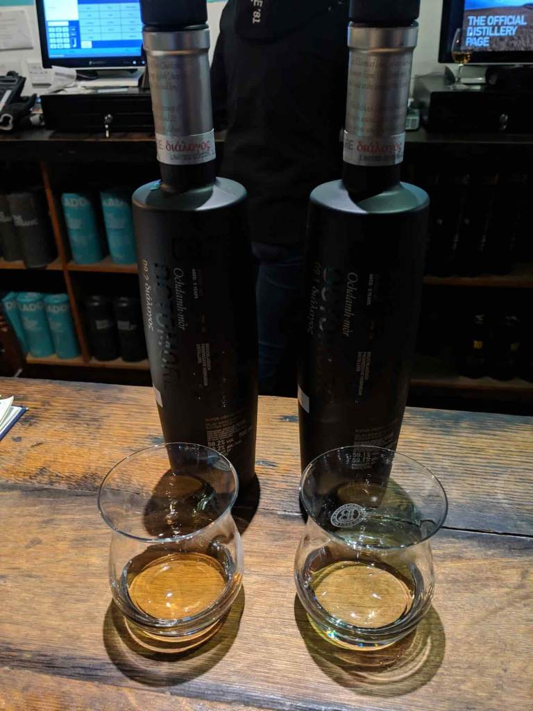 Two black bottles of whisky in front of tasting glasses